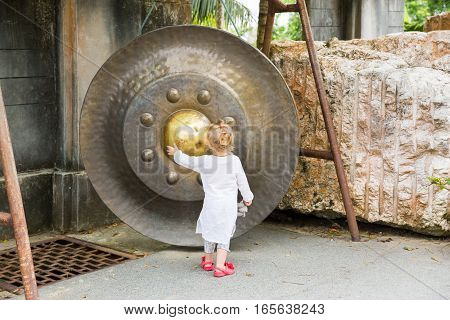 Child near Thai gong in Phuket. Tradition asian bell in Buddhism temple in Thailand. Famous Big bell wish near Gold Buddha