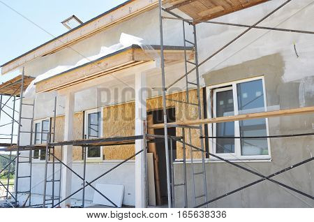 Construction and Renovation of the Rural House with Eaves Windows Doorway Fixing Facade Insulation Plastering and Painting Exterior House Wall.