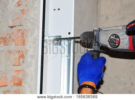 Contractor Installing Garage Door. Repairman uses automatic screwdriver to drill the wall for garage door installation.