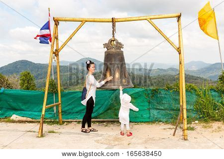 Child and mom near Thai gong in Phuket. Tradition asian bell in Buddhism temple in Thailand. Famous Big bell wish near Gold Buddha