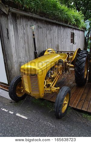 old yellow farm tractor stands near wooden barn with grassy roof outdoors on summer day