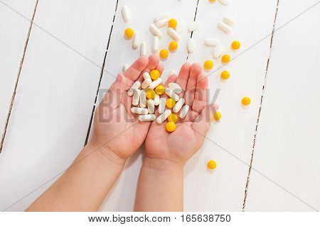 Child's hands holding pills and vitamins. Close up