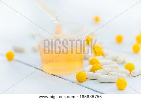Pills and beaker with mixture on white background