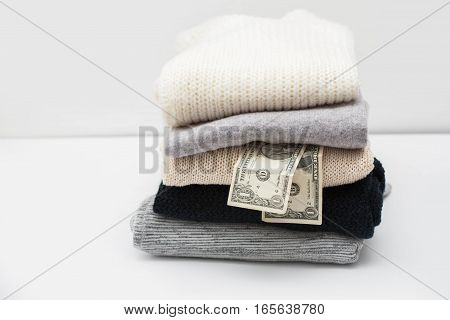 Stack of sweaters and couple of dollars