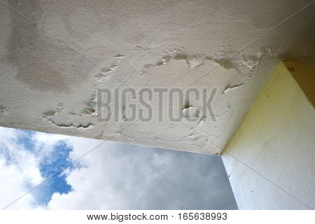 Rain water leaks on the ceiling causing damage peeling paint and moldy.