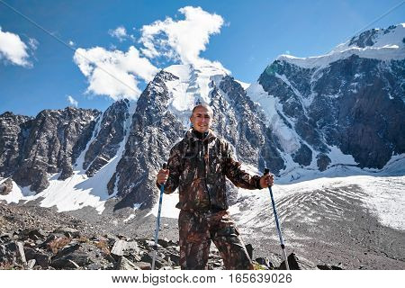 Survival in the wild. A man in camouflage resting among the mountains. Stalker survive in the woods. Lake in the mountains. Snowy peaks Altai
