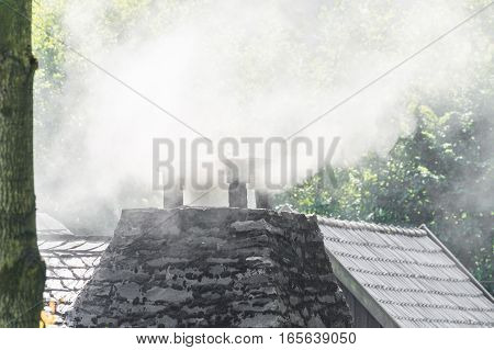 Smoking chimney on the roof of a house.