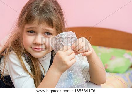 Five-year Girl Listens To Burst Like Bubbles On The Packaging Bag