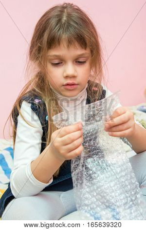 Five-year Girl Sitting On The Bed And Eats Bubbles Packaging Package