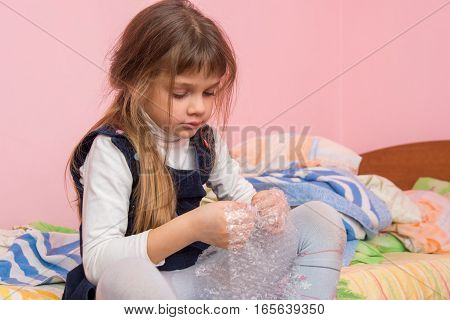 Sad Girl Sitting On The Bed And Eats Bubbles On The Packaging Film