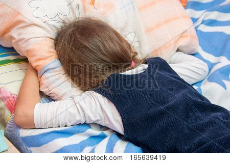Upset Little Girl Crying With His Face Buried In The Pillow