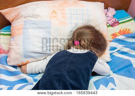 Five-year Girl Crying With His Face Buried In The Pillow