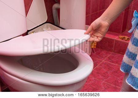 Child's Hand Lifts The Lid Of The Toilet, Close-up