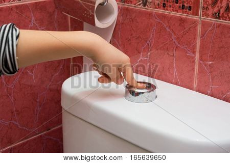 Child's Hand Finger Presses The Button On The Water Draining Into The Toilet Bowl, Close-up