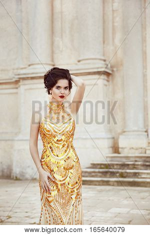 Fashion Shot Of Stunning Elegant Woman In Luxurious Golden Dress. Beautiful Young Brunette Model In