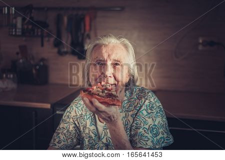 Very elderly woman eating a piece of pizza at home. Unhealthy diets.