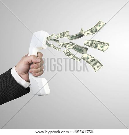 Hand Holding Telephone Handset With Money Spraying Out
