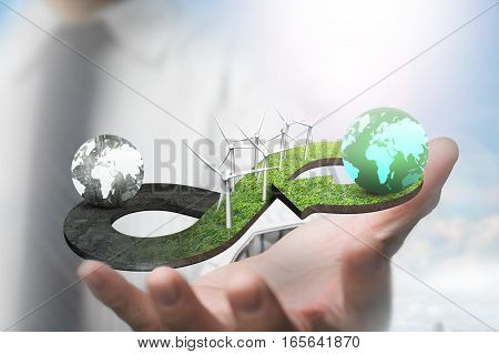 Green circular economy concept. Hand showing arrow infinity symbol of grass texture with wind turbines and two globes of different colors.