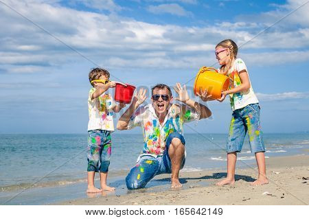 Father and children playing on the beach at the day time. People having fun outdoors. Concept of friendly family.