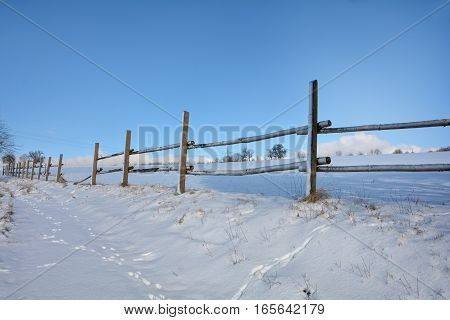 Wooden fence in winter with snow and blue sky
