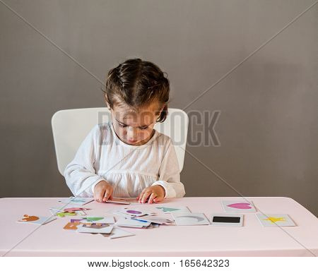 Cute little girl in white shirt playing puzzle. Process of education cognition