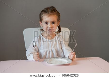 Cute little girl sitting on table with plate holding fork and spoon in hands