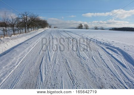 snow-covered street in snowy scenery with many ripe tracks