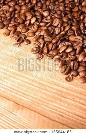 Roasted Coffee Beans Spread Over On Wooden Table.