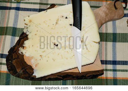 Cutting board with slice of pecorino cheese