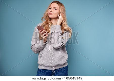 Cute Positive Blonde Woman In Hoodie Listening Music