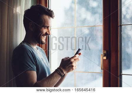 Young bearded man standing by the window using a smartphone
