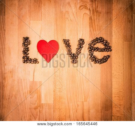 Coffee beans on wood background. Shape of word Love made from coffee beans, decorated with red heart on wooden surface. Roasted coffee beans on rustic wood background. Top view. Copy space.