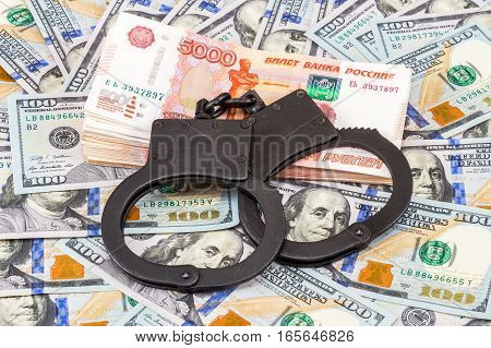 Black steel handcuffs lying on the heap of money