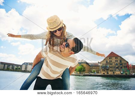 Laughing Young Man And Woman Piggy Back Riding