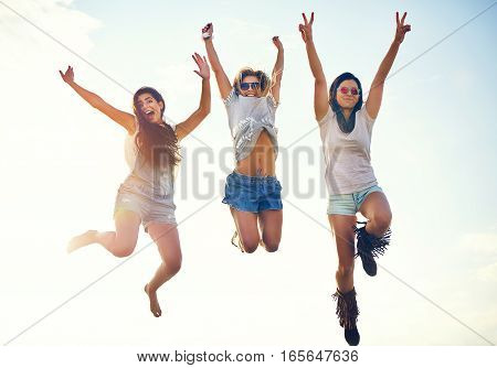 Three Agile Energetic Teenagers Leaping In The Air