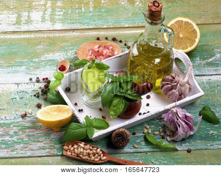 Arrangement of Freshly Made Creamy Pesto Sauce in Glass Gravy Boat with Raw Ingredients and Olive Oil in White Wooden Tray on Cracked Wooden background