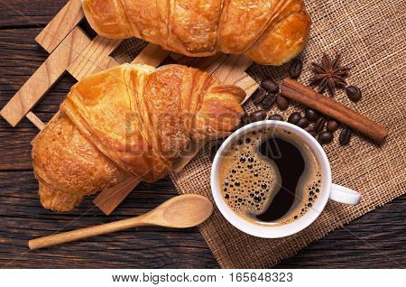Cup of coffee and croissants on rustic wooden table top view