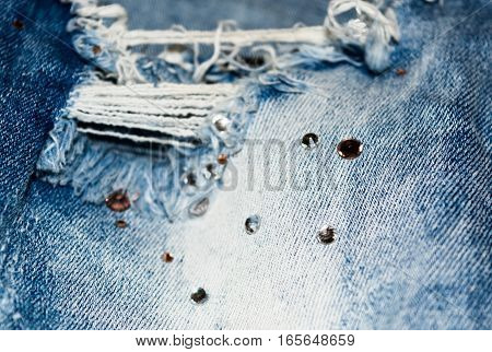 Detail of torn jeans with rhinestones. Denim texture. The rectangular background.