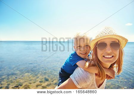 Woman Holding Son On Back On Seaside