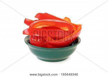 Sliced red bell pepper in green plate on a white background.
