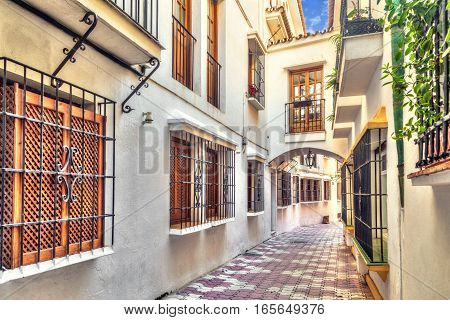 Narrow street with bridge between houses in old town of Marbella Andalusia Spain