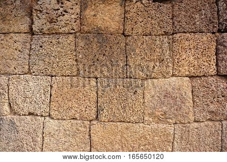 Irregular wall made of yellow volcano stone cubes. The rectangle and square blocks vary in size and shape and have a porous surface, creating a very individual pattern. The wall is part of a temple in the ancient ruins of Angkor.