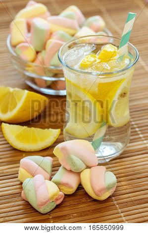 Lemonade with fresh lemon. Lemon water and sweets.