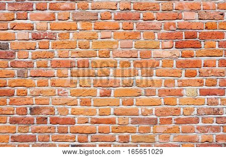 brick wall - different sized and colored (red, orange and yellow) bricks with gray seams make an irregular brickwork pattern. A vintage style background texture representing old constructions and buildings.