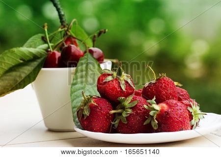 Group of fresh spring fruits together cherries and strawberries. Cherries in white bowl.Strawberry on a wooden background. Red strawberries. Strawberries on green