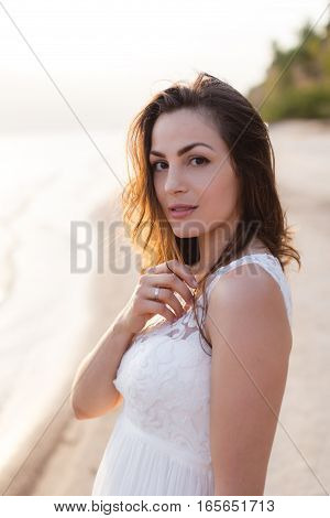 Beautiful Young Brunette Woman In White Long Dress At The Sea Shore