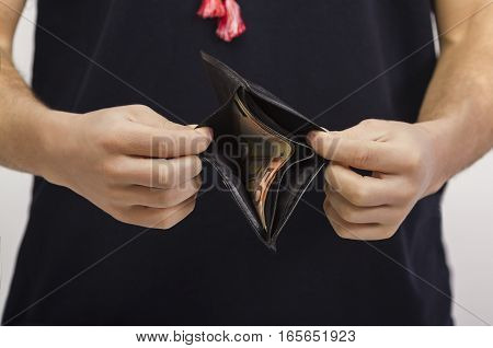 man holding a wallet with money on a light background