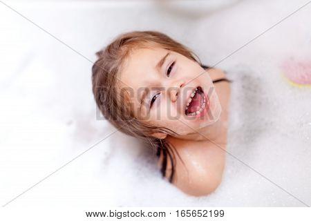 Small pretty girl is taking a bath with a foam