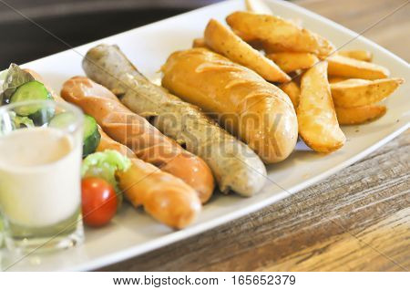 mixed sausage with French fries and vegetable