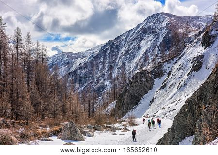MUNCH-SARDYK BURYATIA RUSSIA - April 30.2016: Group of climbers goes on channel frozen river in mountains of Eastern Sayan. Climbing mountain peaks of East Siberia.